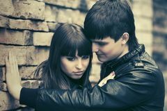 Счастливые молодые пары моды в кожаных куртках на кирпичной стене стоковое фото rf