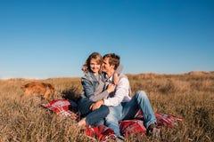 Счастливые молодые пары обнимая и смеясь над outdoors стоковое фото