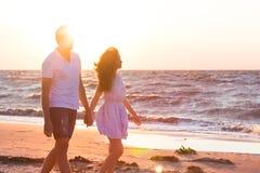 Счастливые молодые пары ослабляя на пляже на заходе солнца мечт каникула стоковая фотография rf