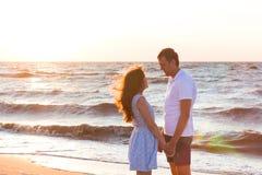 Счастливые молодые пары ослабляя на пляже на заходе солнца мечт каникула стоковые фотографии rf