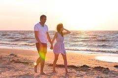 Счастливые молодые пары ослабляя на пляже на заходе солнца мечт каникула стоковые изображения rf