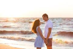 Счастливые молодые пары ослабляя на пляже на заходе солнца мечт каникула стоковое изображение rf