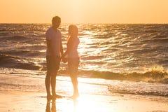 Счастливые молодые пары ослабляя на пляже на заходе солнца Путешествовать семьи Стоковые Фото