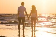 Счастливые молодые пары ослабляя на пляже на заходе солнца Путешествовать семьи Стоковая Фотография RF