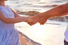 Счастливые молодые пары ослабляя на пляже на заходе солнца Путешествовать семьи стоковое фото rf