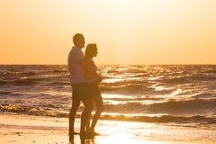 Счастливые молодые пары ослабляя на пляже на заходе солнца Путешествовать семьи стоковое изображение rf