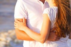Счастливые молодые пары ослабляя на пляже на заходе солнца Путешествовать семьи стоковое изображение