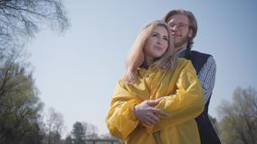 Счастливые молодые пары отдыхая outdoors Довольный красивый бородатый парень со стеклами обнимая милую девушку со светлыми волоса сток-видео