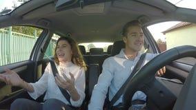 Счастливые молодые пары потехи смеясь над совместно в автомобильном сток-видео