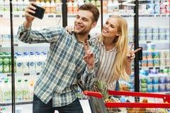 Счастливые молодые пары принимая selfie Стоковое фото RF