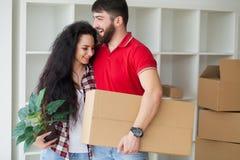 Счастливые молодые пары распаковывая или коробки упаковки и двигая в a Стоковые Фотографии RF