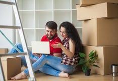 Счастливые молодые пары распаковывая или коробки упаковки и двигая в a Стоковая Фотография RF
