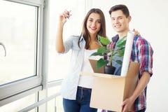 Счастливые молодые пары распаковывая или коробки упаковки и двигая в a Стоковое Фото