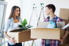 Счастливые молодые пары распаковывая или коробки упаковки и двигая в a Стоковое Изображение RF