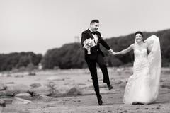 Счастливые молодые пары свадьбы имея потеху на пляже Черно-белый стоковое изображение
