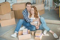 счастливые молодые пары сидя совместно и усмехаясь на камере пока коробки упаковки Стоковые Изображения RF