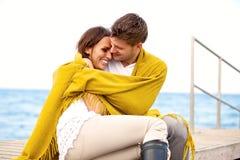Счастливые молодые пары сидя совместно на пристани Стоковая Фотография