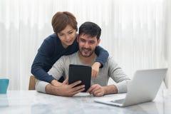 Счастливые молодые пары с таблеткой стоковое фото rf