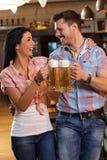 Счастливые молодые пары clinking с пивом в pub стоковые фотографии rf