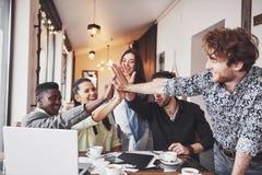 Счастливые молодые предприниматели в вскользь одеждах на таблице кафа или в офисе давая высокие fives друг к другу если Стоковые Фотографии RF