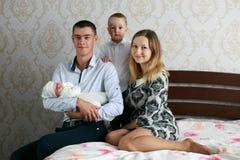 Счастливые молодые родители с 2 детьми стоковая фотография rf