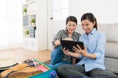 Счастливые молодые сестры держа передвижной компьютер пусковой площадки Стоковые Изображения