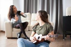 Счастливые молодые сестры имея потеху в живущей комнате Стоковые Фото