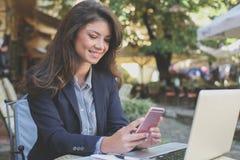 Счастливые молодые сообщения чтения бизнес-леди на кафе Стоковая Фотография