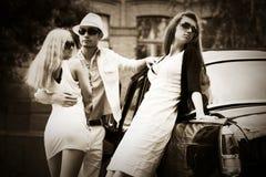 Счастливые молодые человек и женщины моды рядом с винтажным автомобилем Стоковое Фото