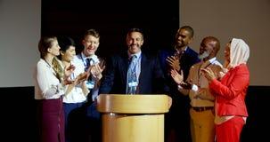 Счастливые мульти-этнические бизнесмены аплодируя зрелому бизнесмену на этапе в семинаре 4k акции видеоматериалы