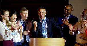 Счастливые мульти-этнические бизнесмены аплодируя зрелому бизнесмену на этапе в семинаре 4k сток-видео