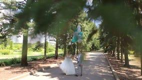 Счастливые новобрачные идя в парк с воздушными шарами акции видеоматериалы
