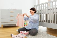 Счастливые одежды младенца установки беременной женщины дома стоковое фото rf