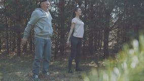 Счастливые отец и дочь разрабатывают в предыдущем лесе 4K видеоматериал