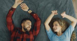 Счастливые падения молодой женщины и человека на серую кровать в комнате Любовники смотря друг к другу акции видеоматериалы