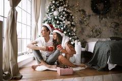 Счастливые парень и девушка в белых футболках и шляпах Санта Клауса сидят с красными чашками на поле перед окном рядом с стоковая фотография rf