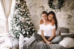 Счастливые парень и девушка сидящ и обнимающ на кровати с серым одеялом в уютной украшенной комнате с деревом Нового Года стоковые изображения rf