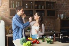 Счастливые пары варя здоровую еду совместно Стоковые Изображения