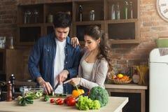 Счастливые пары варя обедающий совместно стоковая фотография rf