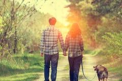 Счастливые пары влюбленн в собака идя на сельскую дорогу стоковые изображения