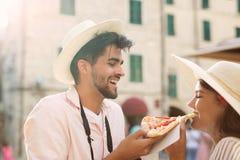 Счастливые пары в влюбленности деля пиццу Стоковые Фотографии RF
