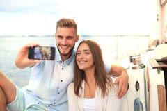 Счастливые пары в влюбленности принимая selfie на паруснике, ослабляя на яхте на море стоковая фотография