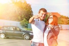 Счастливые пары в как раз купленной влюбленности, новым автомобилем от торговца и владением k Стоковая Фотография