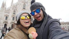 Счастливые пары в милане есть мороженое принимая фото автопортрета selfie на каникулах путешествуют в Италии снеговик песка океан видеоматериал
