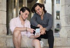 Счастливые пары гея с их мобильным телефоном стоковая фотография