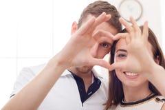 Счастливые пары делая влюбленность подписывают с пальцами Стоковая Фотография RF