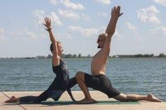 Счастливые пары делая йогу около воды на пляже стоковое изображение rf