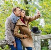 Счастливые пары делая selfie на мобильном телефоне Снаружи в парке осенью Стоковые Фотографии RF