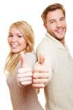 Счастливые пары держа большие пальцы руки вверх Стоковое Фото