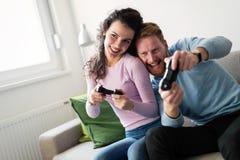 Счастливые пары играя видеоигры дома Стоковые Изображения